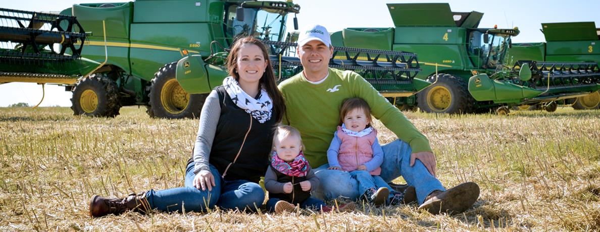 Family sitting in field in front of farm equipment