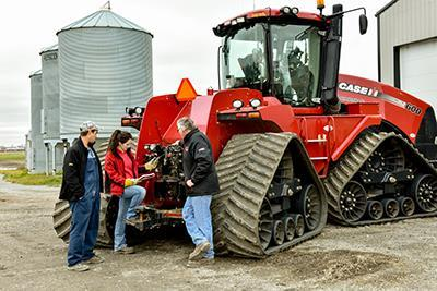 People beside agricultural equipment
