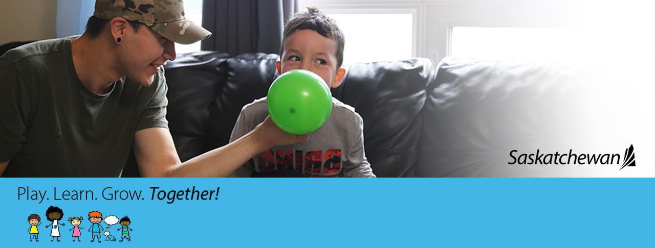 father helping son blow up a balloon