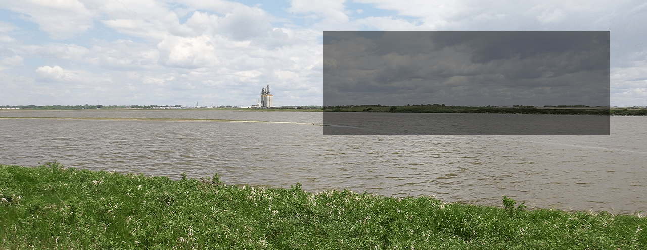 Image of lake in Northern Saskatchewan with a grain elevator in teh background.