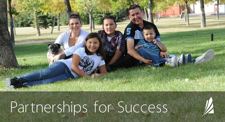 """An image showing a happy Indigenous family sitting in the grass with text that reads, """"Partnerships for Success."""""""