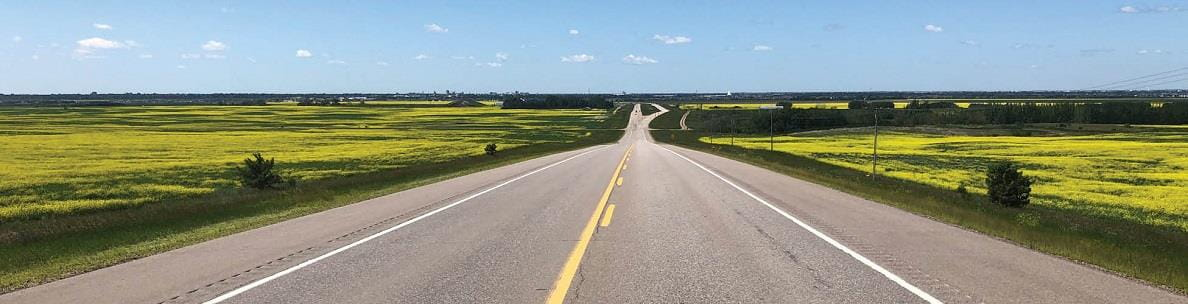 Two lane highway with canola fields on the right and left sides.