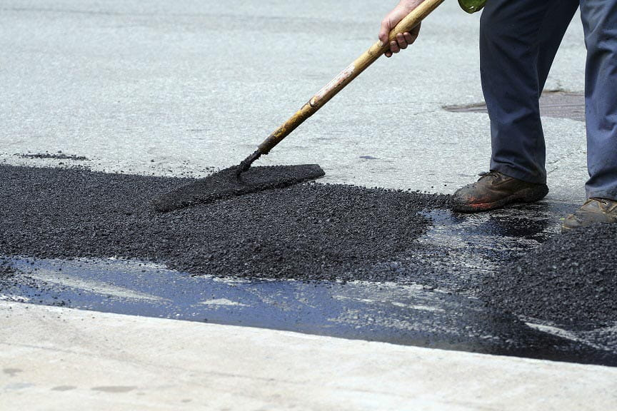 pushing asphalt with a tool