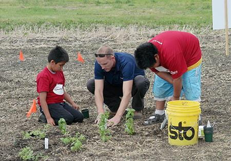 Adult and children planting