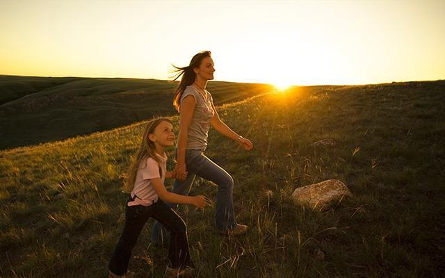 Mother and daughter walking on a hill