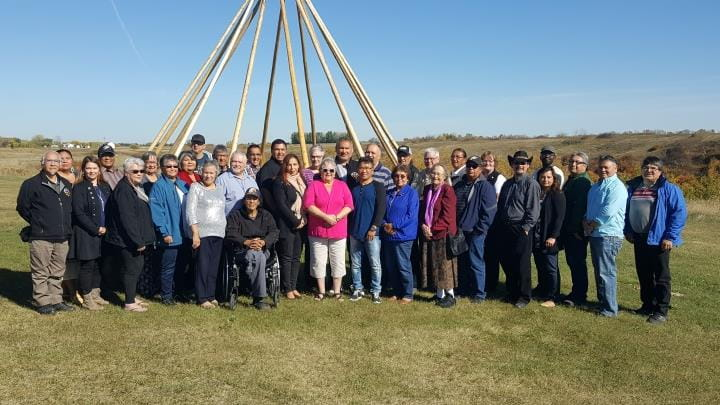 Over 30 members of the Elders Forum pose on a grassy plain.